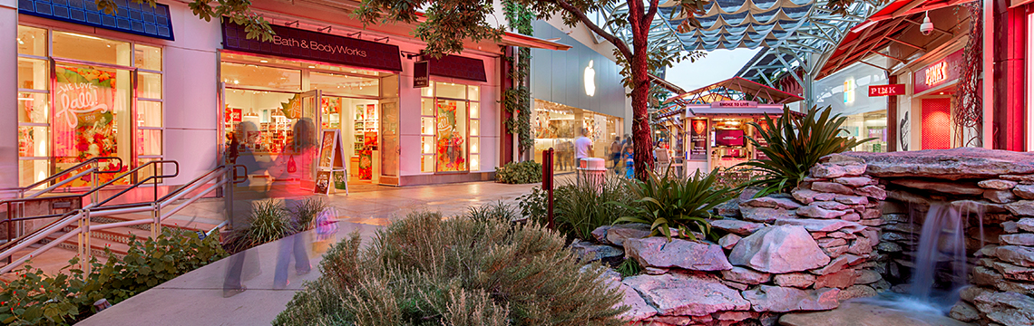 Shoppers stroll past a water fountain and illuminated storefronts at The Shops at La Cantera.